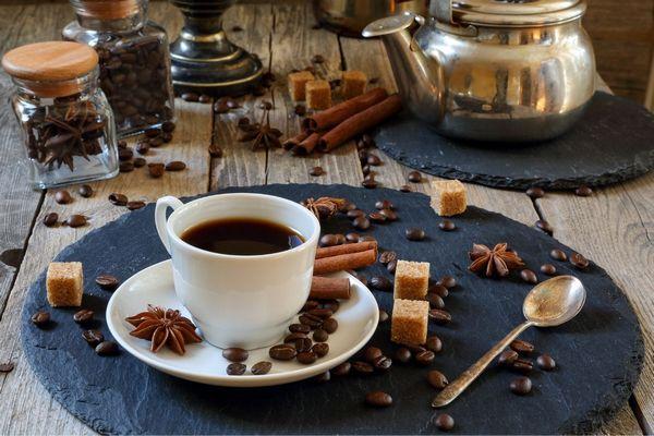 Egy asztalon üvegekben és mellettük fahéj, csillagánizs, kávészemek, illetve kockacukor, illetve fém teáskanna, fehér kávéscsészében feketekávé és kanál.