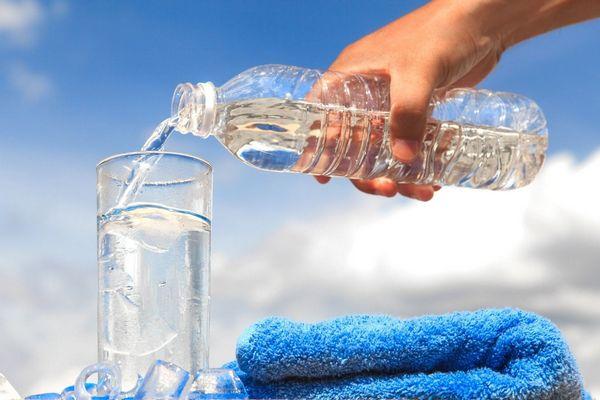 Egy vizespalackból vizet öntenek egy üvegpohárba, mellette kék törölköző.