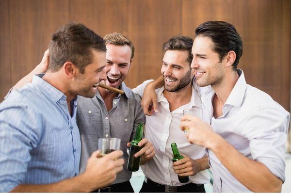 Négy fiatal férfi összeölelkezve nevet, kezükben sörös üveg és boros pohár, egyik szájában szivar.