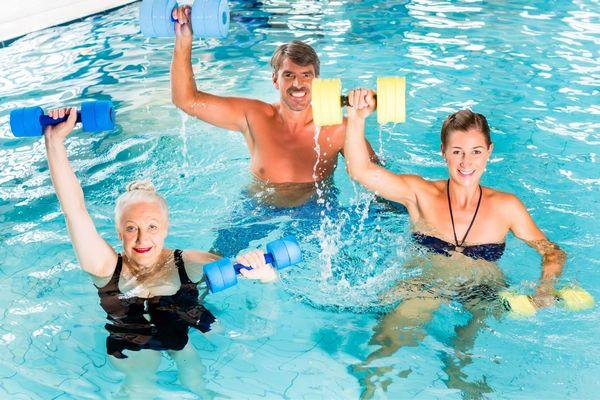 Uszodában középkorú pár és egy idős hölgy kezükben súlyzókkal vízitornáznak.