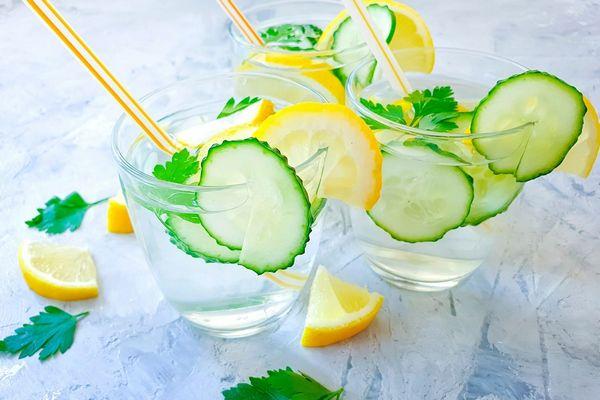 Egy asztalon üvegpoharakban uborkás víz citromkarikákkal és mentalevéllel.