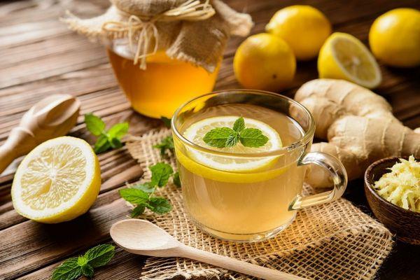 Egy asztalon méz üvegben, egész és félbevágott citromok, mentalevelek, gyömbér, reszelt gyömbér egy tálban, fakanalak és gyömbértea egy üveg teáscsészében.