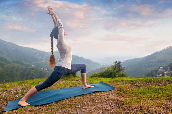 A természetben egy dombtetőn egy fiatal lány jógázik.