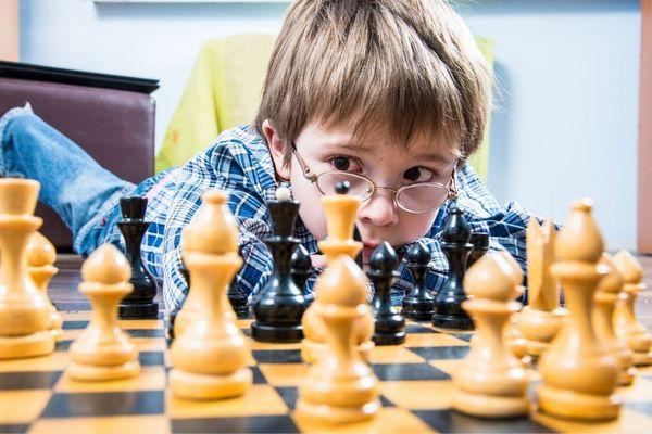 Szemüveges kisfiú hason fekszik egy sakktábla mellett, gondolkodva figyeli a bábukat.