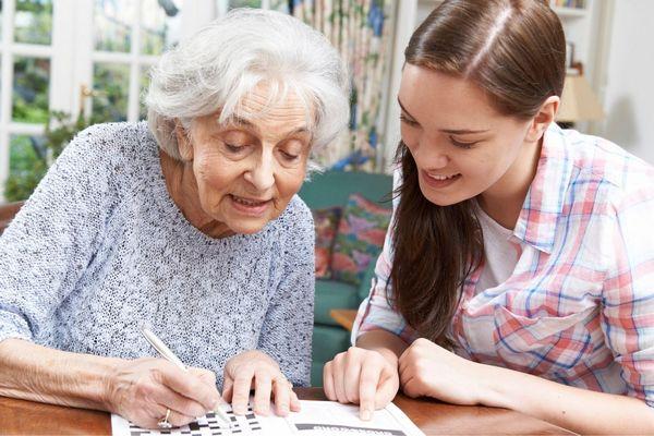 Nagymamájának segít a keresztrejtvény megfejtésében az unoka.