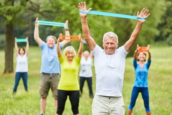 Idősebb emberek a szabadban tornáznak, kezükkel ellenállásedzést végeznek.