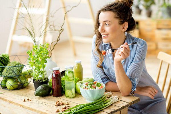 Fiatal hölgy egészséges ételeket eszik, az asztalán avokádó, brokkoli, zöldhagyma, alma, bazsalikom és saláta egy fehér tálban,