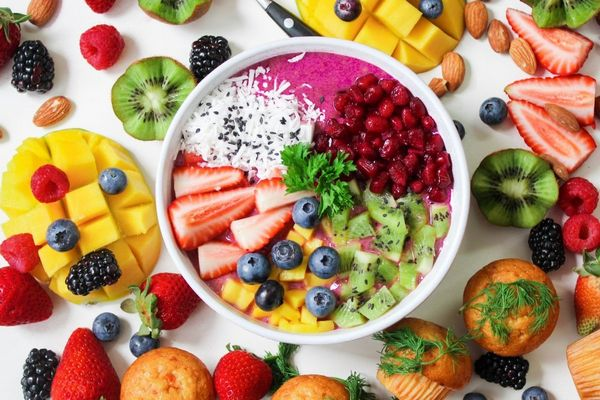 Vitamindús gyümölcsök egy asztalon, mangó, eper, szeder, fekete áfonya, kivi, málna, illetve maffinok és mandula.