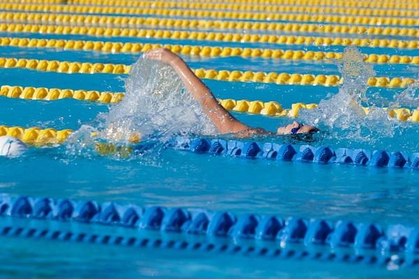 Uszodában egy nő háton úszik.