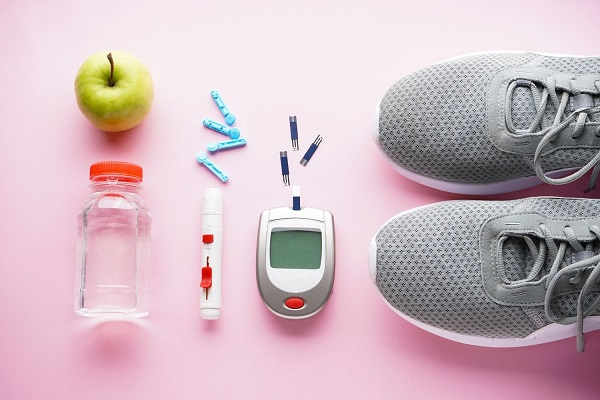 Egy rózsaszín hátterű asztalon egy pár szürke edzőcipő, alma, ivóvíz, vércukorszintmérő és inzulinadagoló.