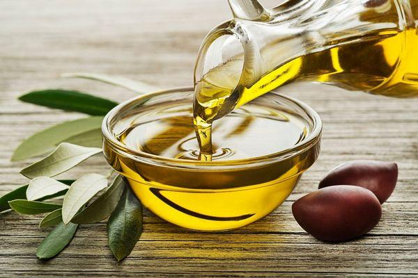 Olívaolajat öntenek egy üvegtálba, mellette olívabogyók és olívalevelek.