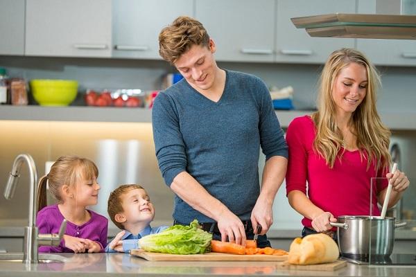 Fiatal házaspár két gyermekükkel a konyhában ebédet főz.