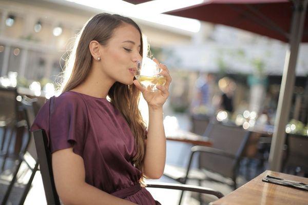 Fiatal hölgy lila ruhában egy kávézóban vizet iszik egy üvegpohárból.