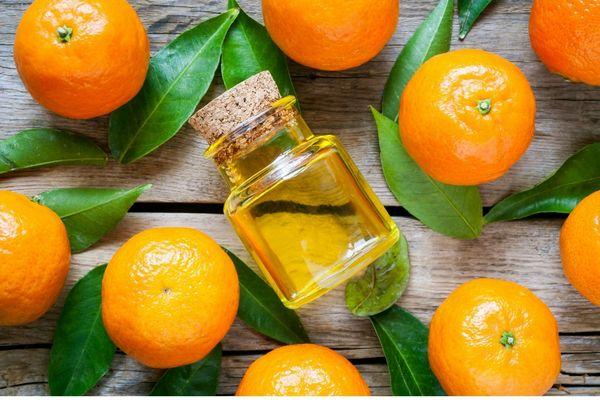 Egy asztalon narancsok és a leveleik, középen egy üvegcsében narancsillóolaj.