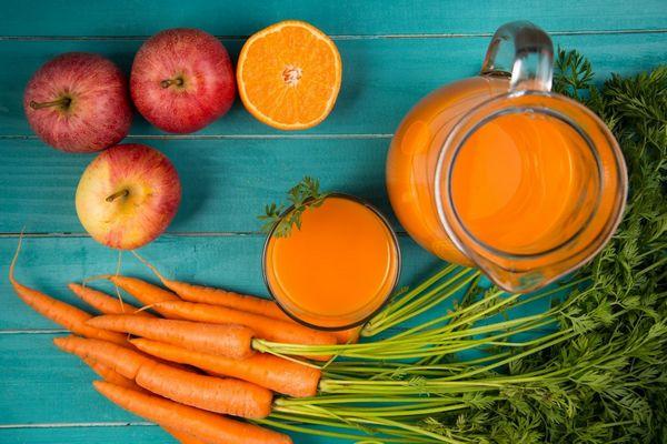 Egy asztalon sárgarépák, almák, félbevágott narancs és narancslé egy kancsóban.