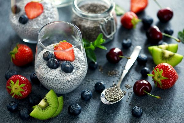 Egy asztalon üvegpoharakban chiamagból készült puding gyümölcsökkel, mellettük eper, fekete áfonya, cseresznye, kivi és egy kanálban chiamagok.
