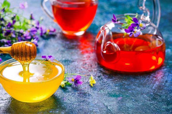 Egy asztalon mézzel teli üvegtál, mellette gyümölcstea üvegkancsóban és üvegbögrében és virágok.