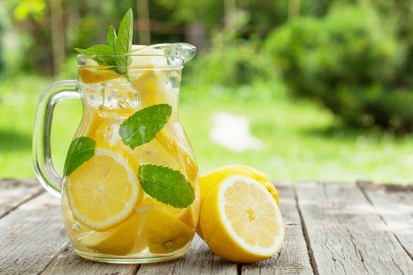 Egy asztalon üvegkancsóban víz, citromlé, citromkarikák és mentalevél.