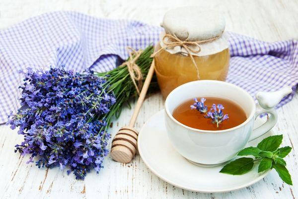 Egy asztalon levendulacsokor, méz egy üvegben, és levendulateát tartalmazó fehér teáscsésze citromfűággal.