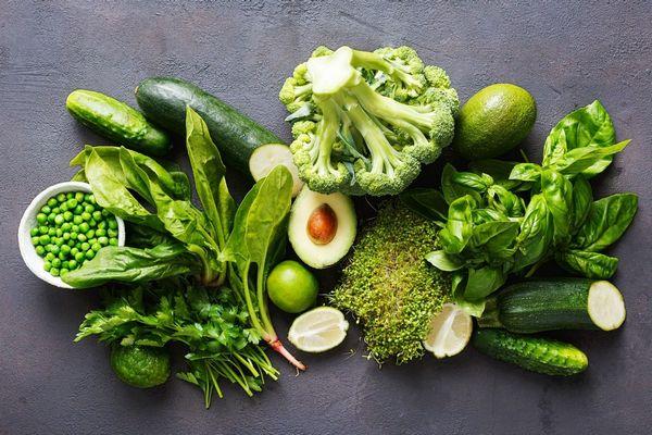 Egy asztalon zöld leveles zöldségek, spenót, petrezselyem, illetve uborba, avokádó, brokkoli, zöldborsó és lime.