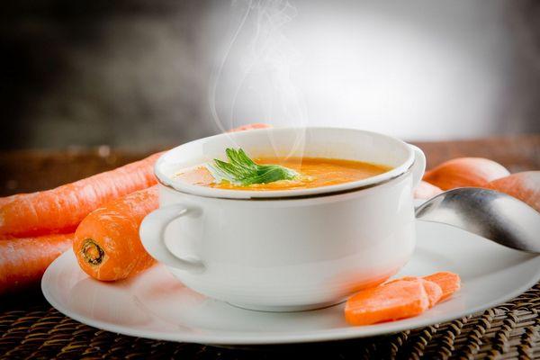 Gyömbéres sárgarépaleves egy tányéron, mellette sárgarépák.