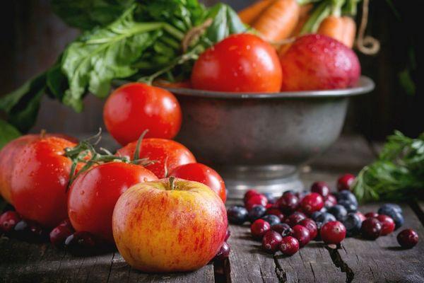 Egy asztalon alma, paradicsomok, piros és fekete áfonya, mellettük egy fém tálban alma, paradicsom, saláta és sárgarépa.