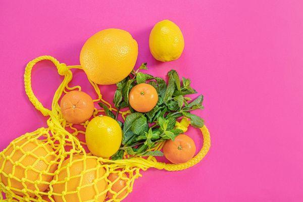 Pink háttér előtt egy sárga hálóban citromok, mandarinok és mentalevelek.