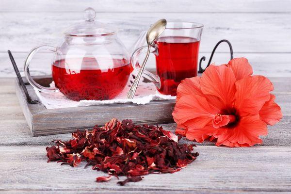 Egy asztalon élő és szárított piros hibiszkuszvirágok, mellettük hibiszkusztea egy üvegkancsóban és üveg teáscsészében.