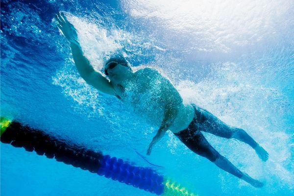 Uszodában fiatal férfi gyorsúszással úszik.
