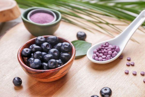 Egy asztalon acai berry gyümölcsök egy tálban, mellette acai berryt tartalmazó étrend-kiegészítő tabletták.