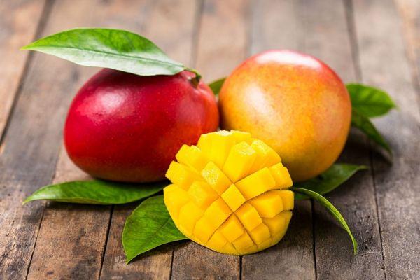 Egy asztalon piros és sárga mangó, mellettük félbevágott mangó.