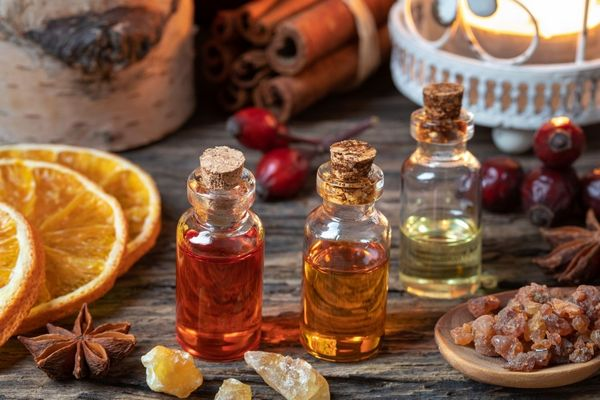 Egy asztalon aszalt narancsok, csillagánizs, illóolajok üvegcsékben, mirhaillóolaj, mirha, csipkebogyó és fahéj.