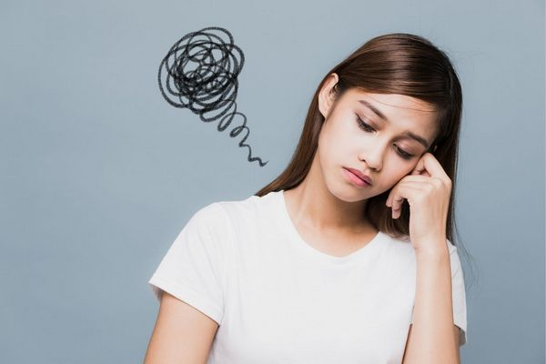 Egy szürke háttér előtt fiatal lány depressziósan néz maga elé, fejét a kezével tartva.