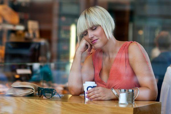 Egy kávézóban fiatal hölgy kávéspoharát fogja, miközben fejét támasztva bóbiskol.