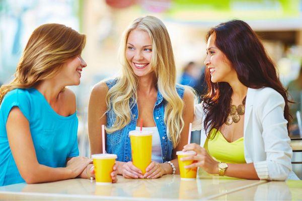 Egy pultnál három fiatal lány vidáman beszélget, kezükben sárga poharakat tartanak.