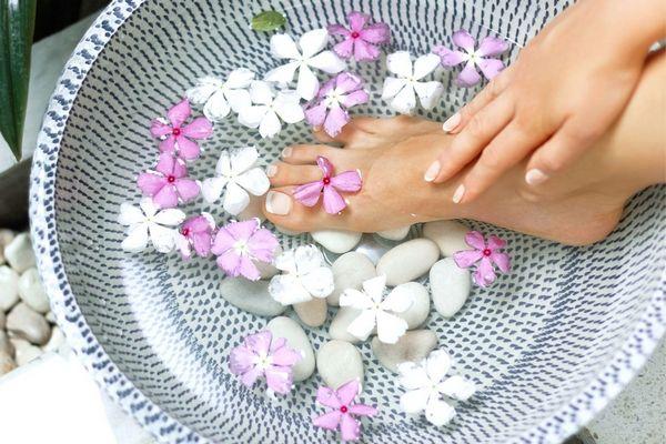 Egy tálban fehér kavicsok, fehér és rózsaszínű virágok és egy női láb, amelyet a keze megérint.