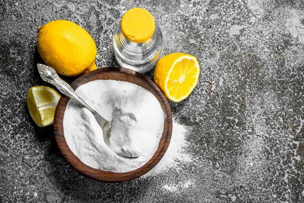 Egész és félbevágott és negyedbe vágott citrom, mellettük egy tálban szódabikarbóna és palackban víz.