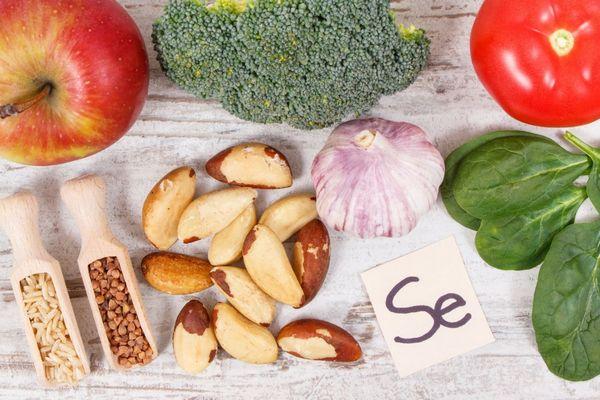 Egy asztalon szelént tartalmazó élelmiszerek, spenót, paradicsom, brokkoli, alma, fokhagyma, brazildió, mandula, hajdina.