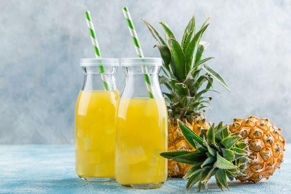 Egy asztalon két ananász, mellettük két üvegben ananászlé szívószállal.