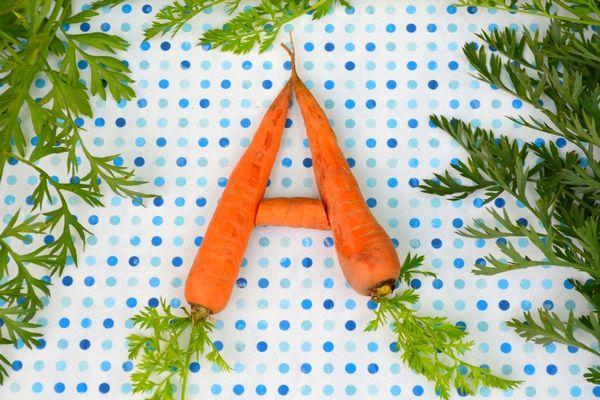 Egy asztalon A betűt formázó sárgarépák.