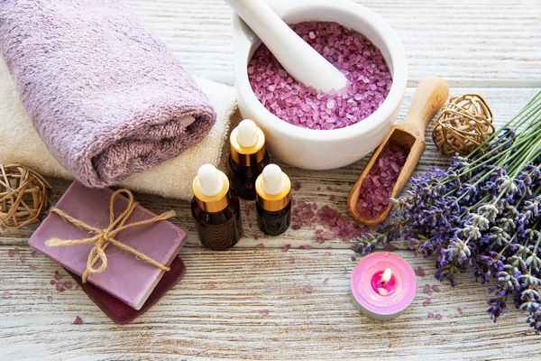 Egy asztalon levendulavirágok, levendula-illóolaj üvegekben, levendulából készült szappan, levendulából készült fürdősó, lila törölköző.