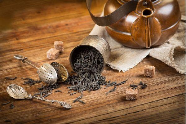 Egy asztalon szálas fekete tea, barna kockacukor, teaszűrő, teáskanál, illetve kerámia teáskanna.