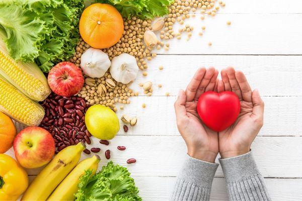 Egészséges táplálékok, saláta, narancs, banán, alma, citrom, bab, pisztácia, fokhagyma, paprika, kukorica, mellettük egy tenyérben tartott piros szív.