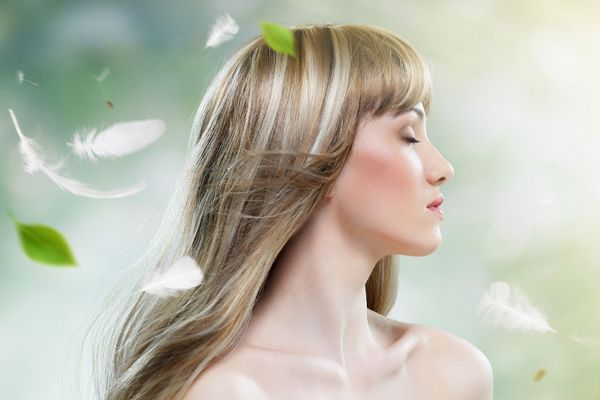 Fiatal hölgy a természeteben kibontott hosszú hajjal.
