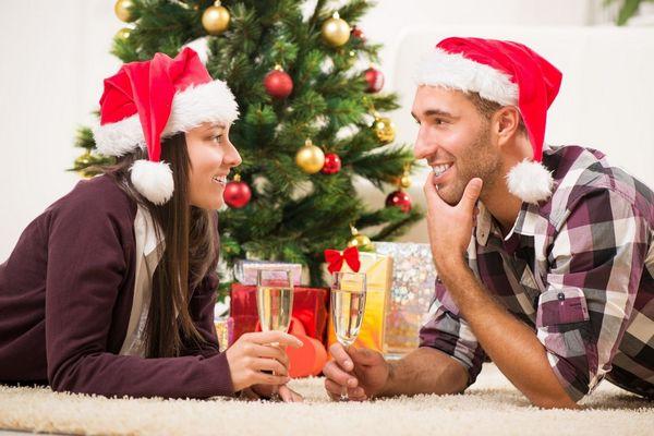 Fiatal házaspár otthon Karácsonykor egymással szemben fekszenek a szőnyegen, kezükben pezsgőspohár, fejükön mikulás sapka.