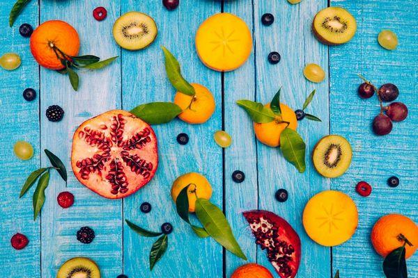Egy kék asztalon citrusos gyümölcsök és leveleik, narancs, citrom, valamint szőlő, kivi, gránátalma, szeder, málna fekete áfonya.