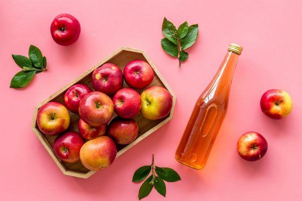 Egy rózsaszín háttér előtt kosárban és mellette almák és üvegben almaecet.