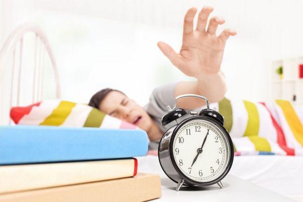 Fiatal ember ágyban fekszik, ébresztőóra felé nyúl.