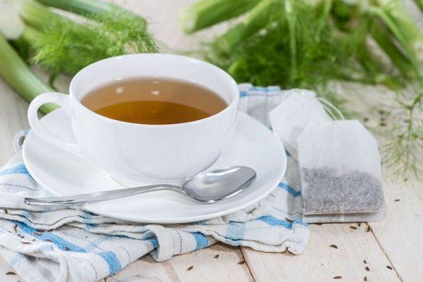 Egy asztalon édesköménytea egy fehér teáscsészében, mellette teafilter, a háttérben édeskömény.