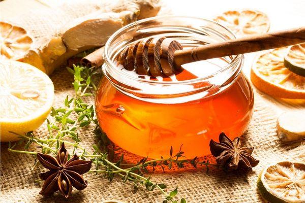 Egy asztalon üvegben méz, mellette citromkarikák, csillagánizsok, gyömbér és rozmaringágak.
